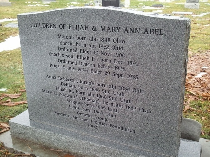 Back of headstone: CHILDREN OF ELIJAH AND MARY ANN ABEL / Moroni: born abt 1848 Ohio / Enoch: born abt 1852 Ohio / Ordained Elder 10 Nov. 1900 / Enoch's son, Elijah Jr.: born Dec. 1892 / Ordained Deacon before 1925; Priest 5 July 1934; Elder 29 Sept. 1935 / Anna Rebecca (Burns); born abt 1854 Ohio / Delilah: born 1856 SLC Utah / Elijah Jr.: born abt 1860 SLC Utah / Mary L. (Stewart) (Thomas): born abt 1862 Utah / Maggie: born 1865 Utah / Flora: born 1869 Utah / Genesis Group / Missouri Mormon Frontier Foundation / 2002
