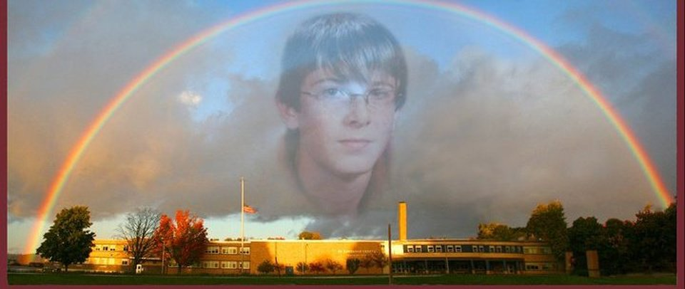 Rainbow stretching over Brasher Falls / St. Lawrence Central High School, with flag at half mast and Kyle Cootware's face Photoshopped over the clouds