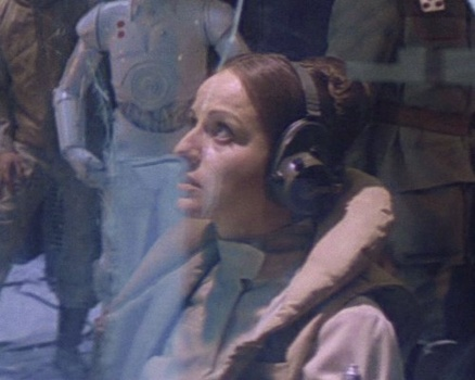 Toryn Farr at Echo Base, looking worried with a white protocol droid in the background