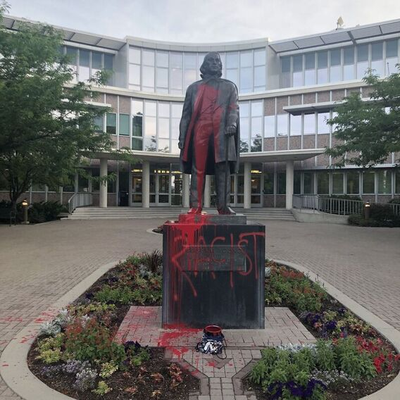 Statue of Brigham Young splattered with red paint and the word