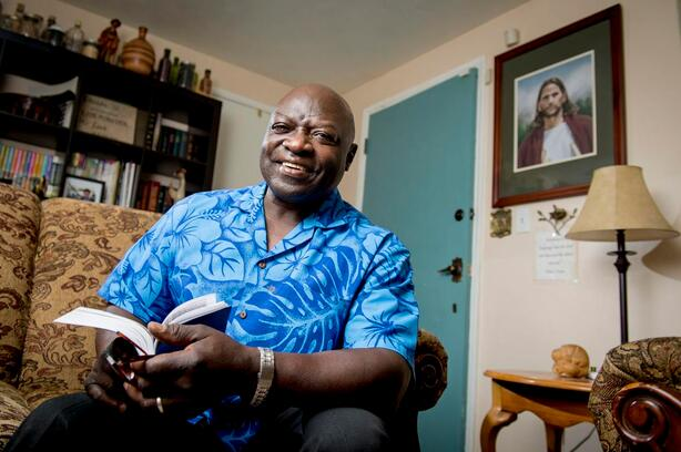 Joseph Freeman sits in his living room smiling and holding a copy of the Book of Mormon.