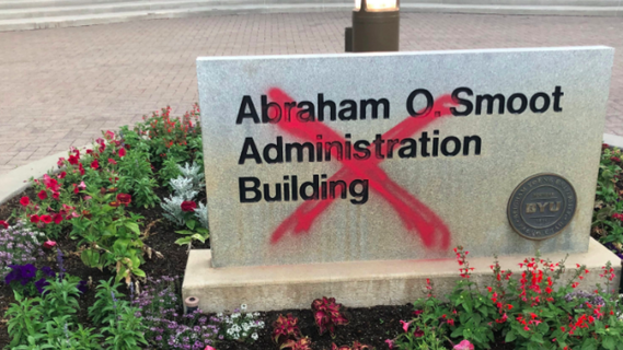 Sign for the Abraham O. Smoot Administration Building at BYU with a red